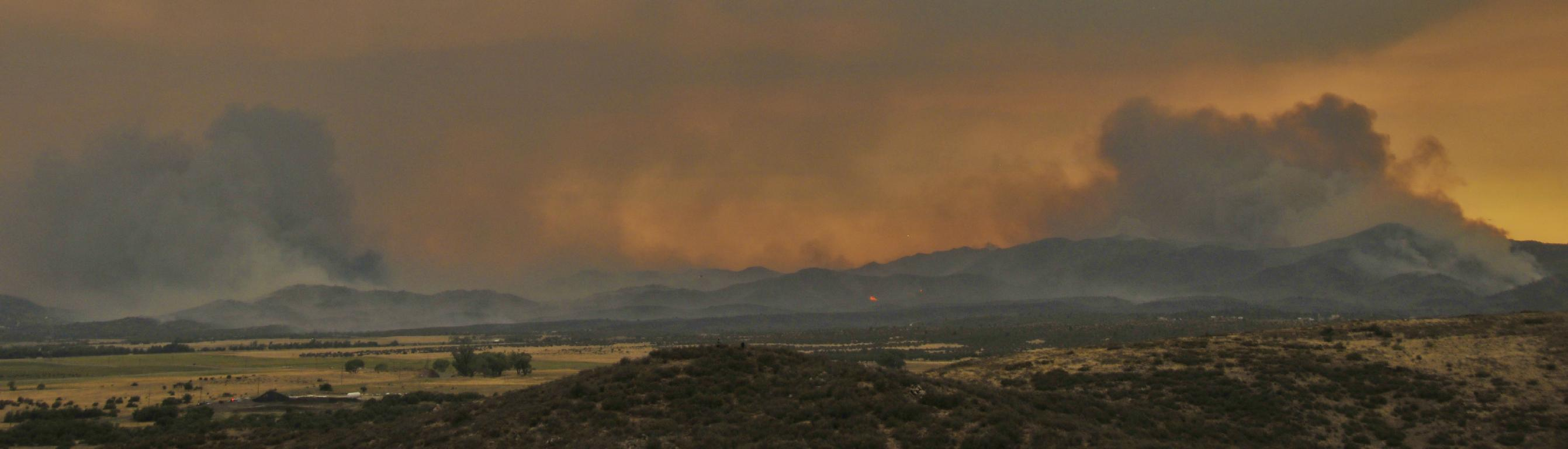 Late day view as fire engulfs Yarnell
